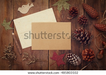 Top view of pine cones and blank card on rustic wooden background. Retro filtered