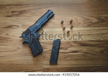 Top view of Pistol semi-automatic .45 caliber with magazine and bullet on the wooden table - stock photo
