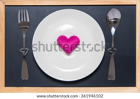 top view of plate with shape of red heart, table spoon and fork