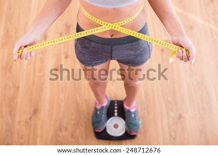 Top view of pretty slim woman with measure around her body is standing on the scales. - stock photo