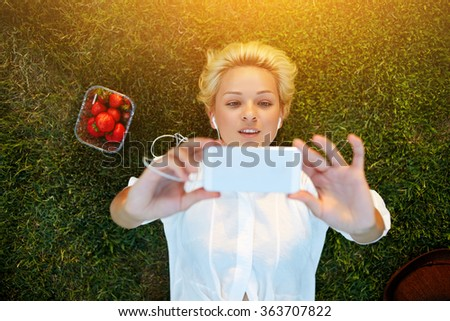 Top view of pretty young woman making self portrait on mobile phone while resting on grass plot in summer day, attractive female student taking picture with cell telephone camera while lying on a lawn - stock photo