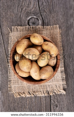 Top view of raw potatoes in bowl on wooden table - stock photo