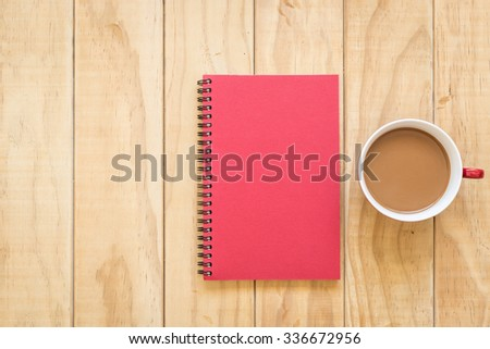 Top view of red book and coffee cup on wooden table background