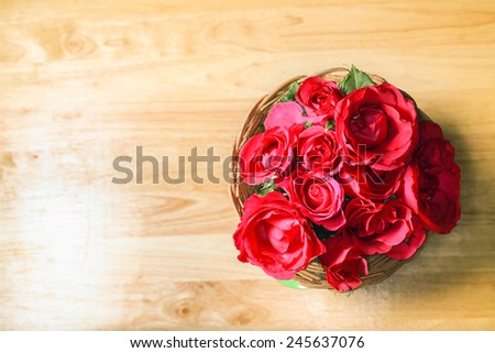 Top view of red roses on the top of wooden desk top, romantic still life. - stock photo