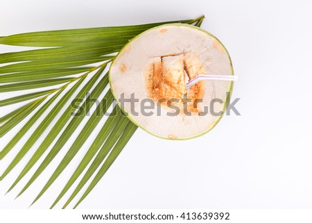 Top view of refreshing green organic coconut fruit juice served with straw on white background - stock photo