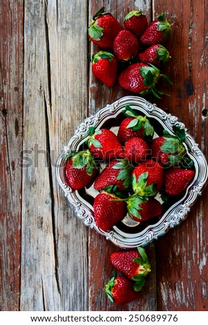 Top view of ripe sweet strawberries on vintage metal plate. Food frame background. - stock photo