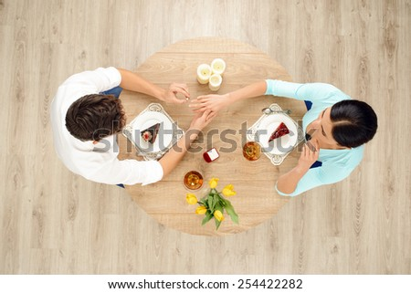 Top view of round table with couple on date. Man putting ring on the right hand of woman. Proposal of marriage concept - stock photo
