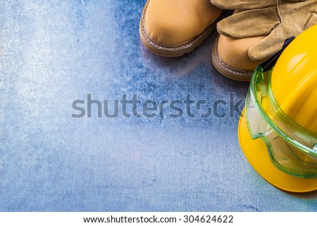 Top view of safety waterproof boots protective leather gloves building helmet and transparent goggles on scratched metallic surface construction concept. - stock photo
