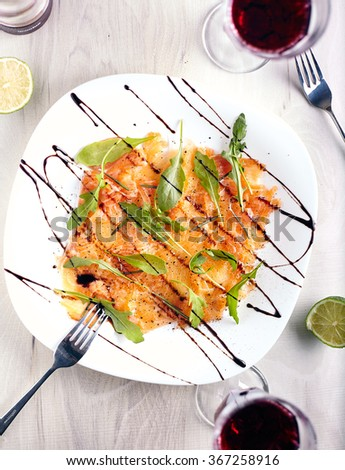 Top view of salmon carpaccio with arugula leaves and sticky balsamic vinegar on wooden background with two glasses of red wine near it. - stock photo