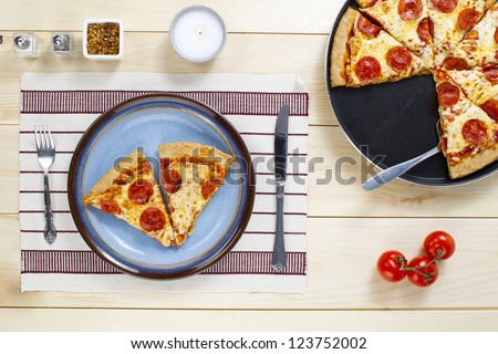Top view of slice of pizza in plate on a restaurant table.