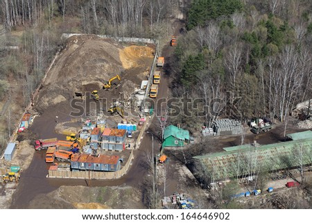 Top view of small construction site with many trucks and machinery in woods. - stock photo