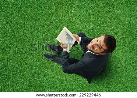 top view of smiley businessman sitting on the green grass and holding touch pad with growing graph - stock photo