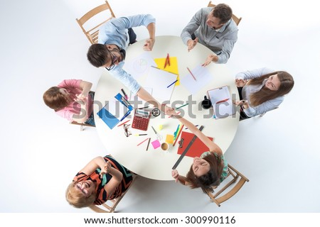 Top view of smilimg business team, sitting at a round table on white background. concept of successful transaction - stock photo