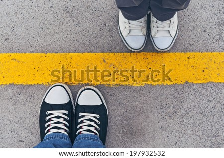 Top View of Sneakers from above, Male and female feet in sneakers standing at dividing frontier line. - stock photo