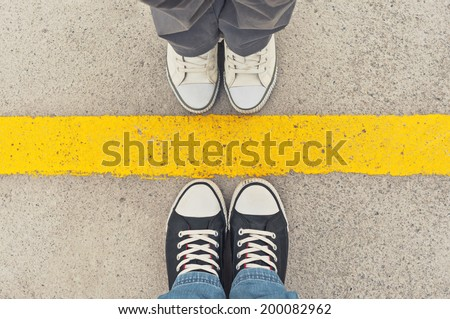 Top View of Sneakers from above, Male and female feet in sneakers, standing at dividing frontier line. - stock photo