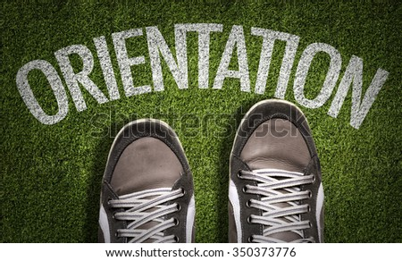 Top View of Sneakers on the grass with the text: Orientation - stock photo