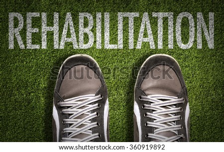 Top View of Sneakers on the grass with the text: Rehabilitation - stock photo
