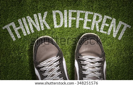 Top View of Sneakers on the grass with the text: Think Different - stock photo