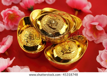 Top view of some chinese gold ingots surrounded by cherry blossoms on a red background - stock photo