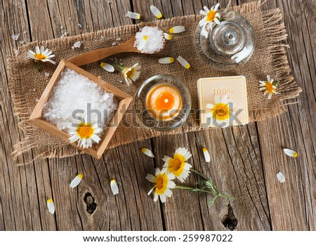 Top view of spa concept with chamomile flowers on a old wooden background - stock photo