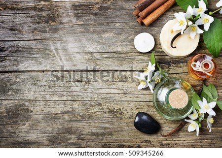 Top view of spa products with copyspace. Essential oils with jasmine, cinnamon and vanilla on grunge rustic wooden table.