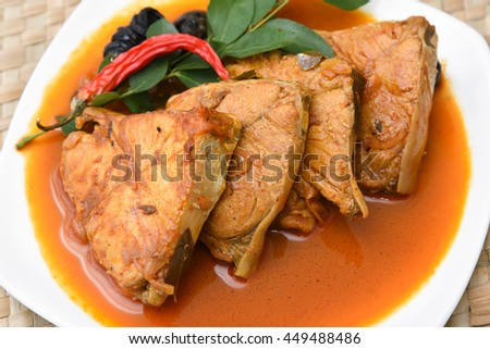 Top view of spicy and hot king fish curry with green curry leaf Kerala India. Barracuda Fish curry with green chili, coconut milk and mango Asian cuisine. - stock photo
