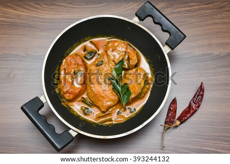 Top view of spicy and hot king fish curry with green curry leaf Kerala India/Indian food. Barracuda Fish curry with red chili, curry leaf, coconut milk and mango Asian cuisine.. - stock photo