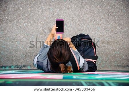 Top view of sporty urban woman texting or messaging on smartphone. Female using her phone at street. - stock photo
