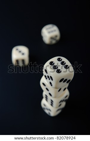 Top view of stacked dices and two single dices on black background - stock photo
