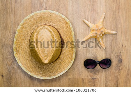 Top view of straw hat, sea star, and pair of glasses on a wooden background. Travel concept - stock photo