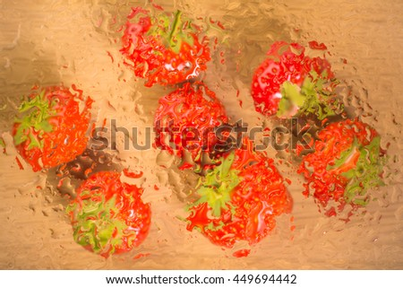 Top view of strawberries under glass surface with water drops - stock photo
