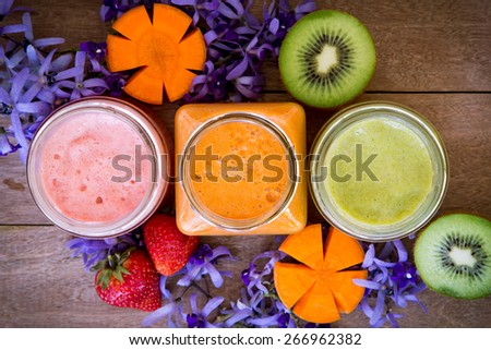 Top view of strawberry,kiwi and carrot juice blended on wooden background - stock photo