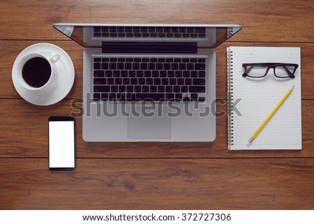 Top view of stuff office desktop. coffee, phone, book, empty screen of smart phone device, vintage tone - stock photo