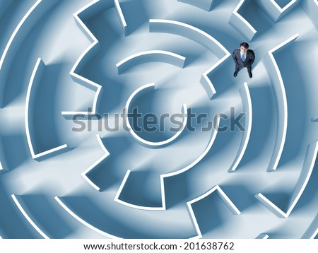 Top view of successful businessman lost in labyrinth - stock photo
