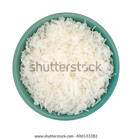 Top view of sweetened coconut flakes filling a small bowl isolated on a white background.