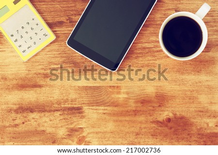 top view of tablet, coffee cup and calculator over wooden textured table background. image is toned. - stock photo