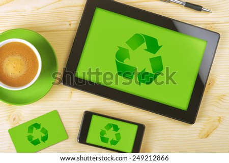 Top View of Tablet Computer, Mobile Phone And Business Card for Recycling Company with Green Background and Recycle Symbol for Corporate Identity Mockup on Office Table. - stock photo
