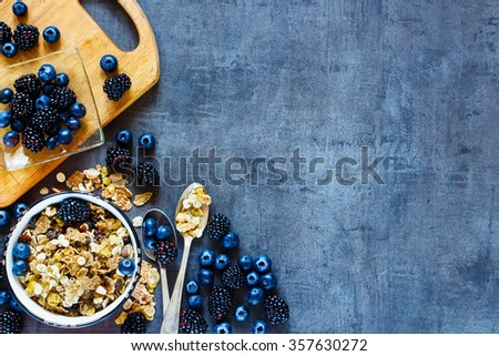 Top view of tasty breakfast table with granola in vintage bowl and dark berries on grunge background. Copy space on right. Organic healthy food and diet concept. - stock photo