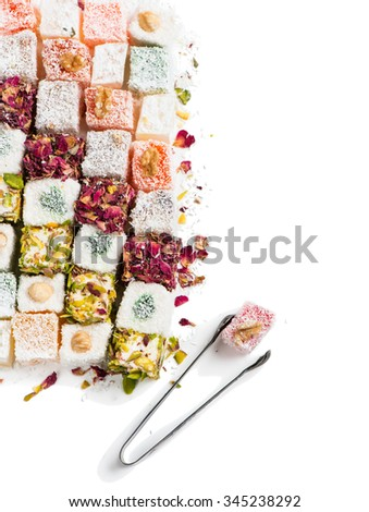 Top view of tasty oriental sweets (Turkish delight lokum) with powdered sugar.  Isolated on white background. - stock photo