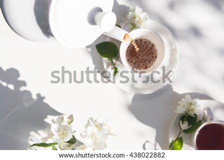 Top view of tea pot flow of tea in the garden. Healthy lifestyle. Sunlight. - stock photo