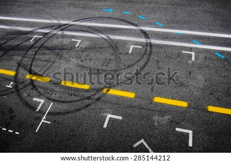 Top view of the asphalt of a car racing pit stop with painted signs and tire marks - stock photo