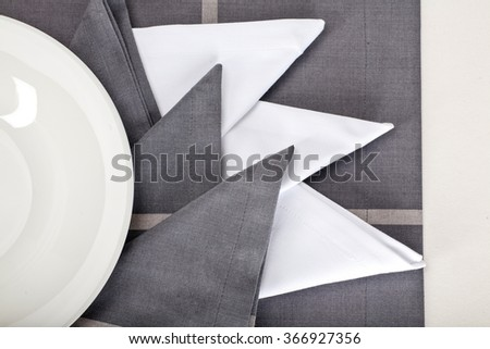 Top view of the beautifully decorated table with white plate and linen napkins on luxurious tablecloth - stock photo
