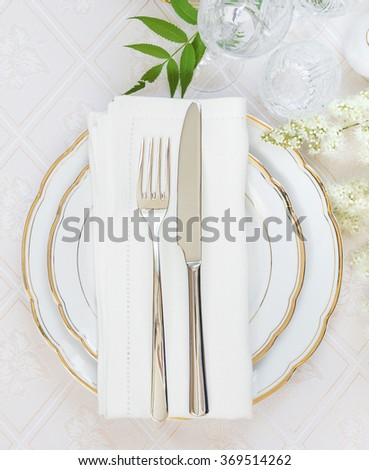 Top view of the beautifully decorated table with white plates, crystal glasses, linen napkin, cutlery and white flower on luxurious tablecloths - stock photo