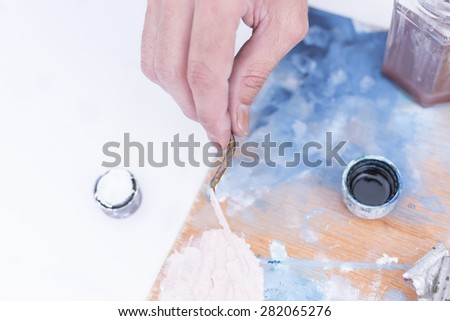 top view of the hand of a male painter mixing paint with the palette knife over the palette at his painting studio - focus on right index finger - stock photo