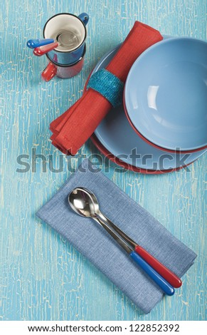 Top view of the kitchen utensils: red and blue plates, cups, spoons and napkins on a blue cracked background - stock photo
