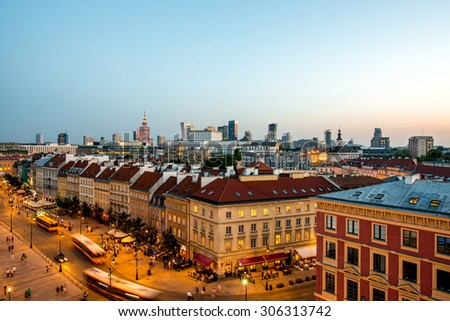 Top view of the old town crowded with people and with business region on the skyline in Warsaw on the evening - stock photo