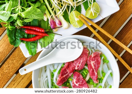 Top view of the Pho Bo on wooden table of street cafe in Vietnam. The Pho Bo is a traditional Vietnamese beef noodle soup with garnish of leaves of cilantro, Asian basil and red chili peppers. - stock photo