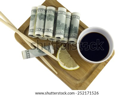 Top view of the rolls of dollars, served on the board with soy sauce, lemon and chopsticks,isolated on white background - stock photo