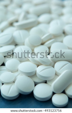 Top view of the Spilled white pills on the blue wooden surface. Focus foreground
