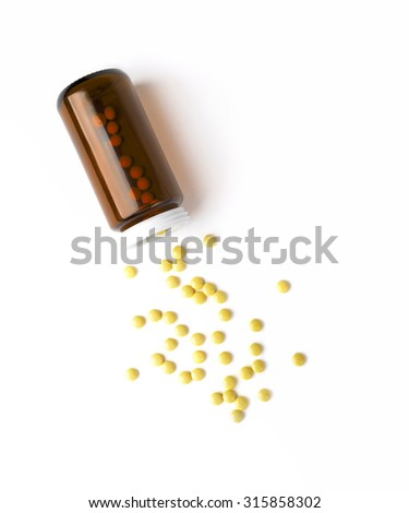 Top view of the spilled yellow pills from the medicine glass bottle. White surface. - stock photo